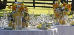Circle tables set with yellow flowers and drinkware
